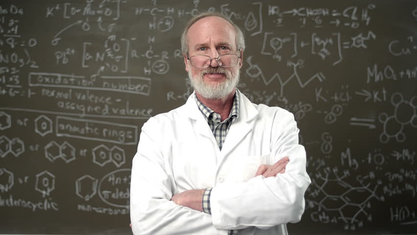 A college professor poses for a portrait with his arms crossed in front of a chalkboard full of equations | Shutterstock HD Video #4746560