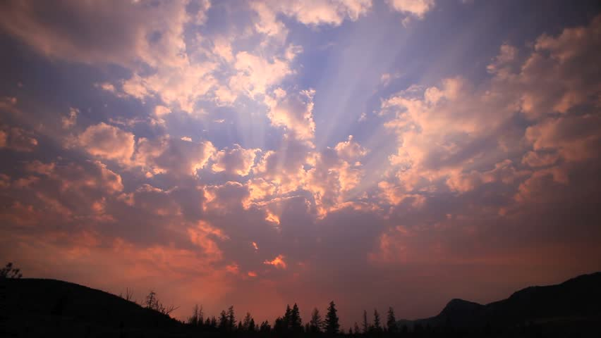 EPIC SMOKEY TIME-LAPSE SUNSET IN A BIG ORANGE AND BLUE SKY  A powerful orange and blue sunset with dancing clouds fill a magnificent cloudy sky above a forested hill.  Contact us for variable speeds.