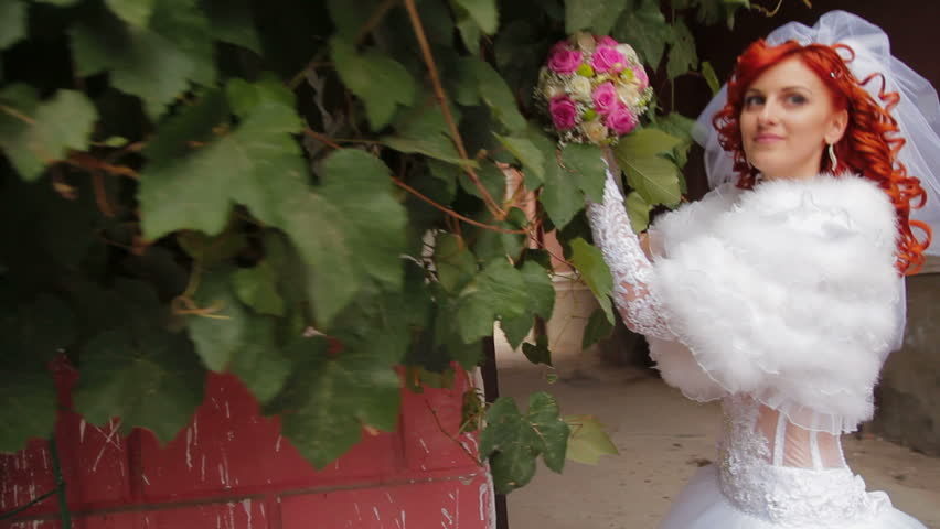 Bride posing for cameras with a wedding bouquet.