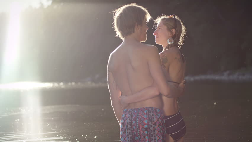 A couple in their bathing suits hug and kiss in the sun, wide shot