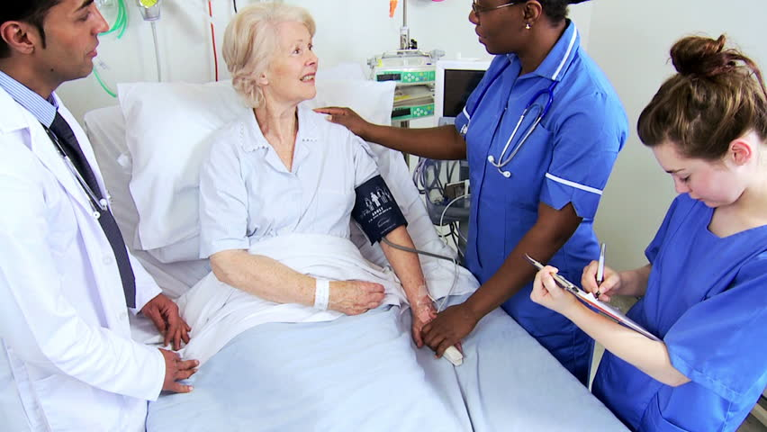 African American nurse taking blood pressure of an elderly Caucasian patient at hospital bedside #4761464