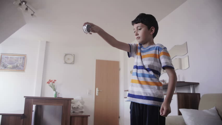 young boy playing with yo yo toy at home in the living room
