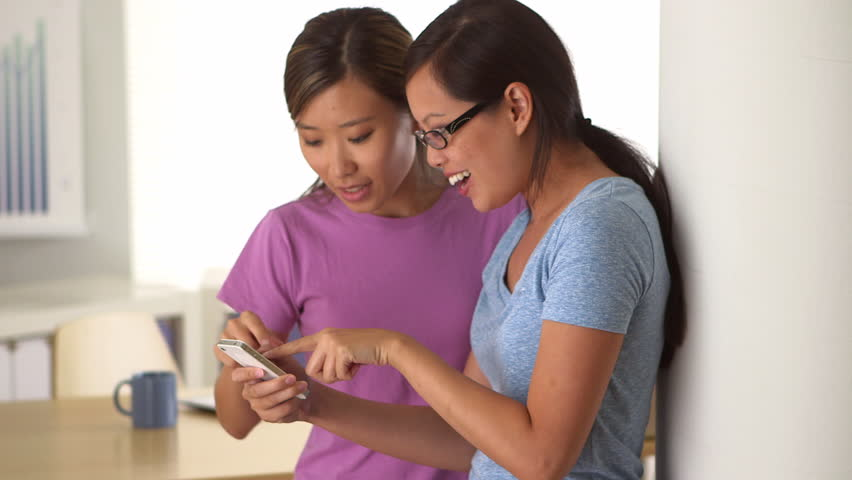 Excited Chinese businesswomen receiving good news on smartphone