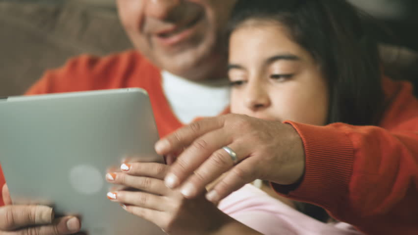 A father sits on the couch and reads a tablet with his daughter