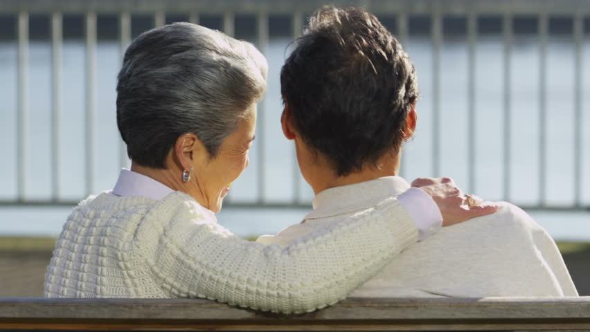 Senior asian couple sitting on bench