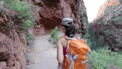 Hiking woman on hike in Zion National Park. Happy woman hiker trekking on walking path in Zion Canyon wearing backpack. Healthy lifestyle image with multiracial Asian Caucasian girl in Utah, USA.