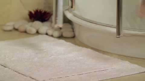 Close up on woman's legs exiting shower. High definition video.