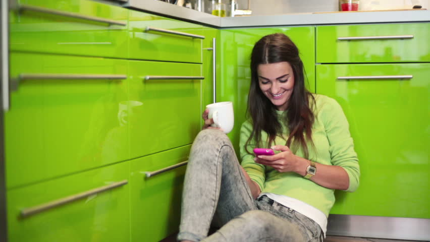 Young woman sitting on floor in kitchen and texting on smartphone    Shutterstock HD Video #4819919