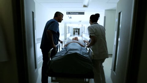 Caring medical staff moving patient on a gurney through hospital corridors