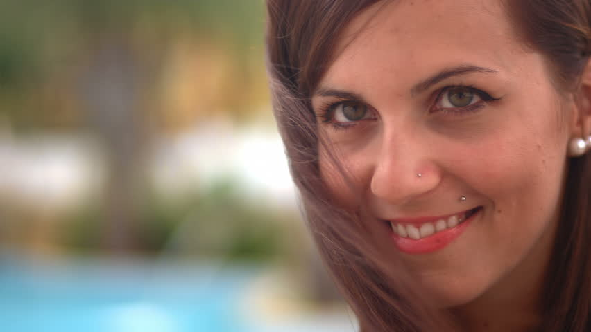 A cute girl by the pool smiles at the camera | Shutterstock HD Video #4821833
