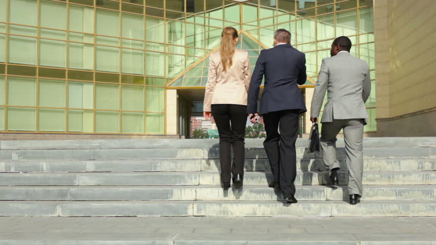 Group of determined business workers walking towards the office building | Shutterstock HD Video #4827344
