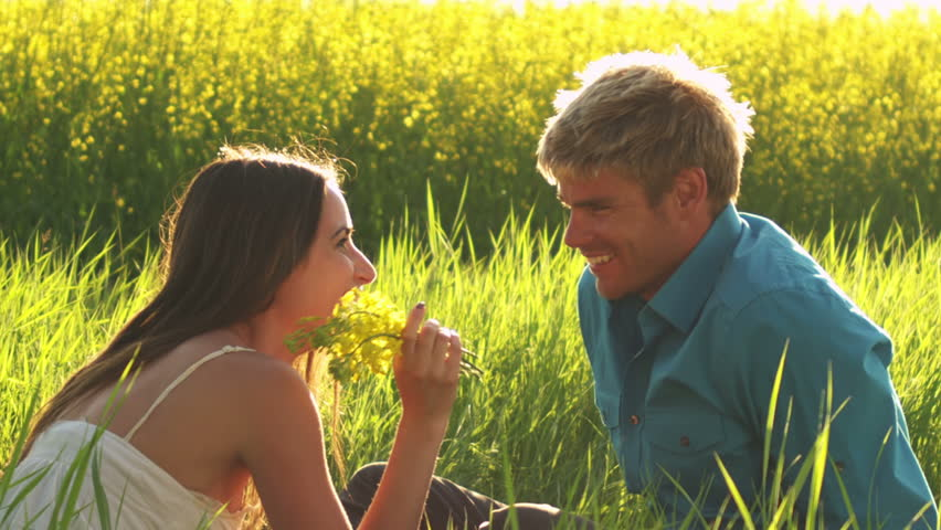 A young couple sits in the grass on a sunny day and look into each other's eyes and love life #4840841