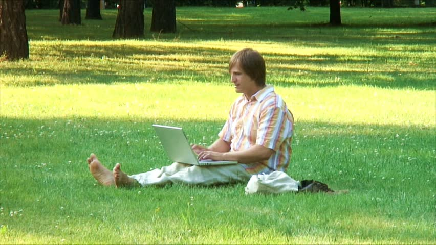 Barefoot man types on laptop siting on a grass in a park