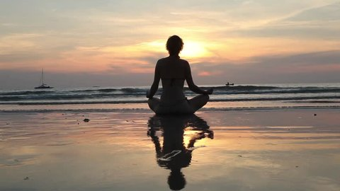 Silhouette young woman practicing yoga on the beach at sunset.(HD)
