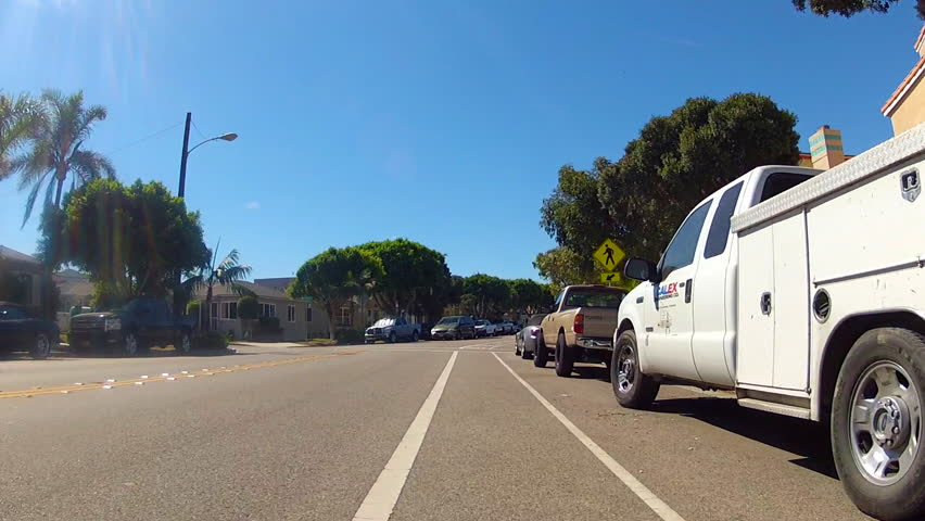 The point of view of someone riding a bicycle in the bike lane of a residential