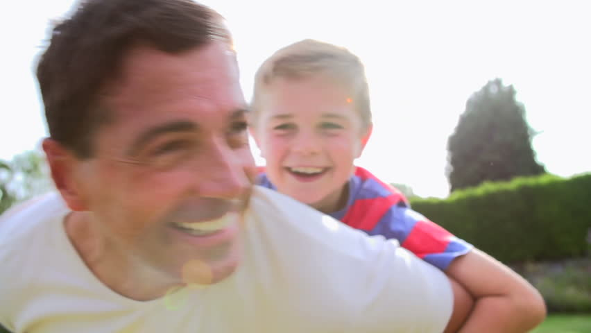 Father giving son piggyback as they spin around in the garden in slow motion