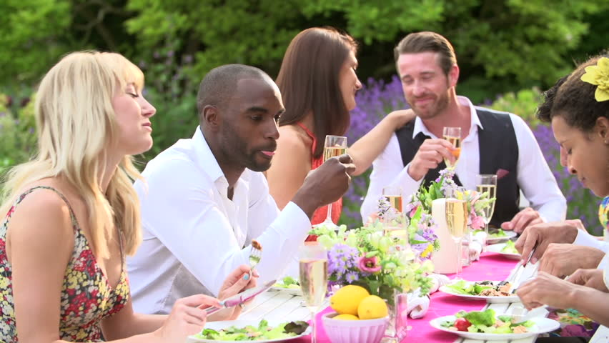 Group of friends laughing and eating at outdoor dinner party in the garden