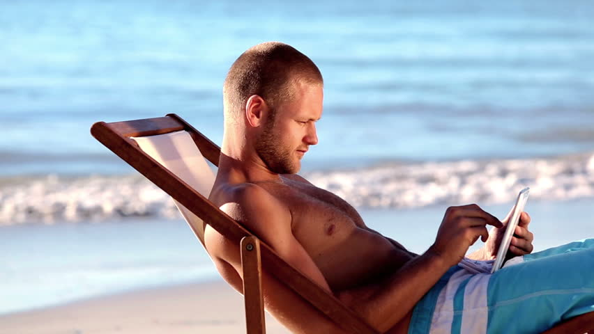 Handsome man sitting on the beach using digital tablet