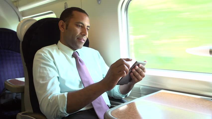 Businessman enjoying book on digital ebook reader device on train journey