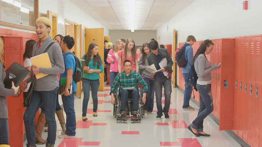 Students empty into the hallway after class and a kid in a wheelchair gets pushed by his friend | Shutterstock HD Video #4893773