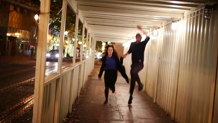 A couple holds hands and runs towards the camera through a tunnel at night
