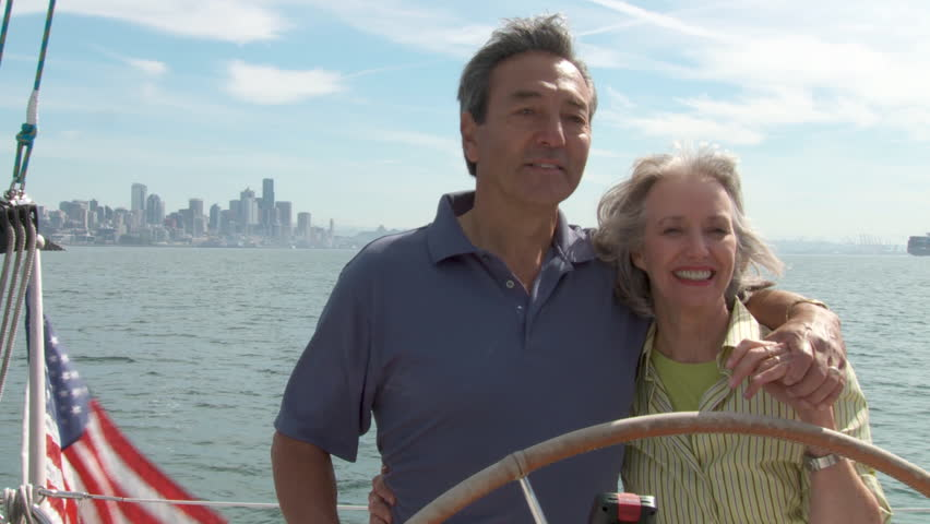 Mature couple at the helm of a yacht on the Puget Sound in Seattle, Washington.