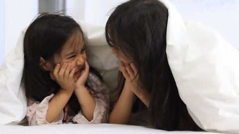 Little Asian girls play hide and seek on the bed, Happy family concept.
