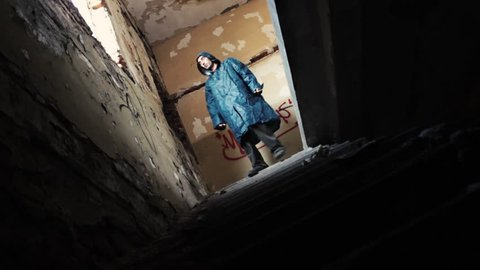 Horror scene, masked killer with machete chasing a girl in abandoned building through the hallways.The girl running down the stairs,murderer with hod go for her.