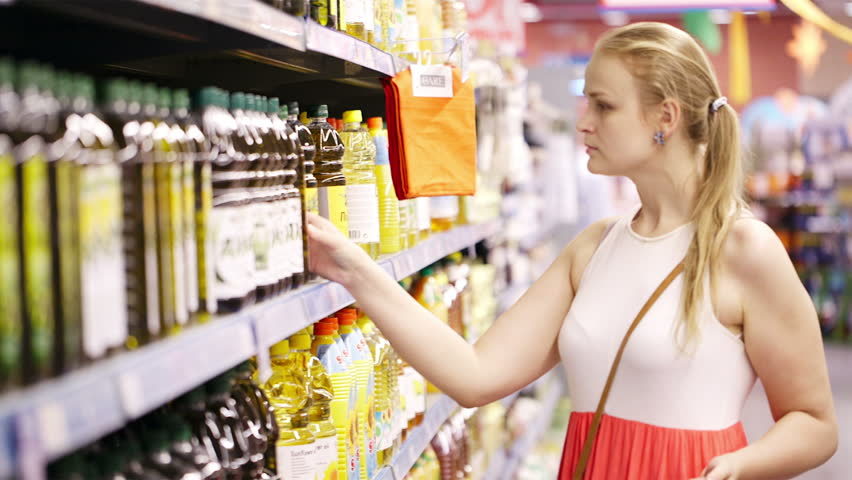 Young blond woman picking an olive oil bottle from the shelves of a supermarket and reading the label | Shutterstock HD Video #4951589