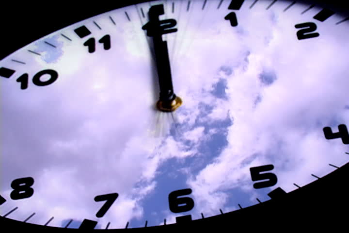 Background of cloudscape reflected on face of circular clock with black background