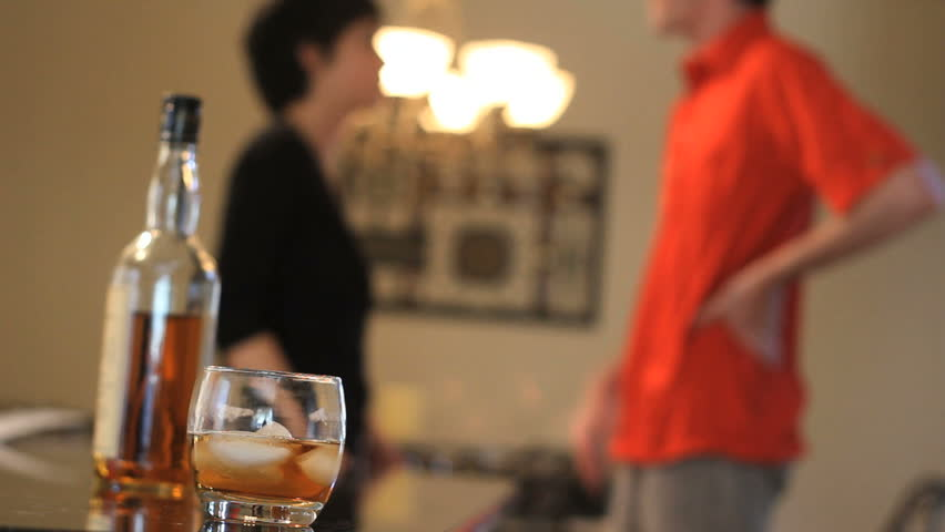 A young couple fights, ending with the woman aggressively slapping her partner. Alcohol in foreground with couple in back.