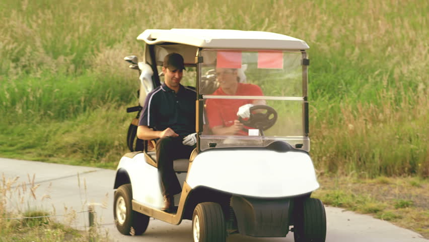 Two men drive a golf cart around a golf course and then stop to play their ball