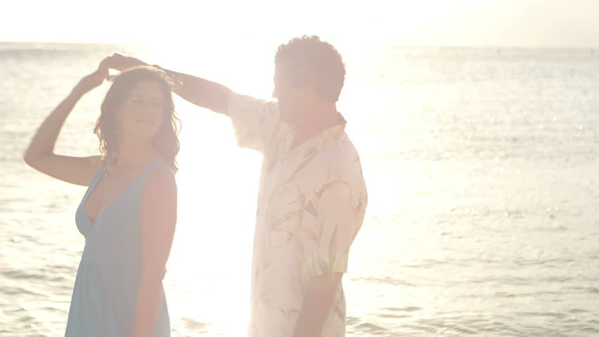 An older couple hug and dance as they stand in the water at the beach