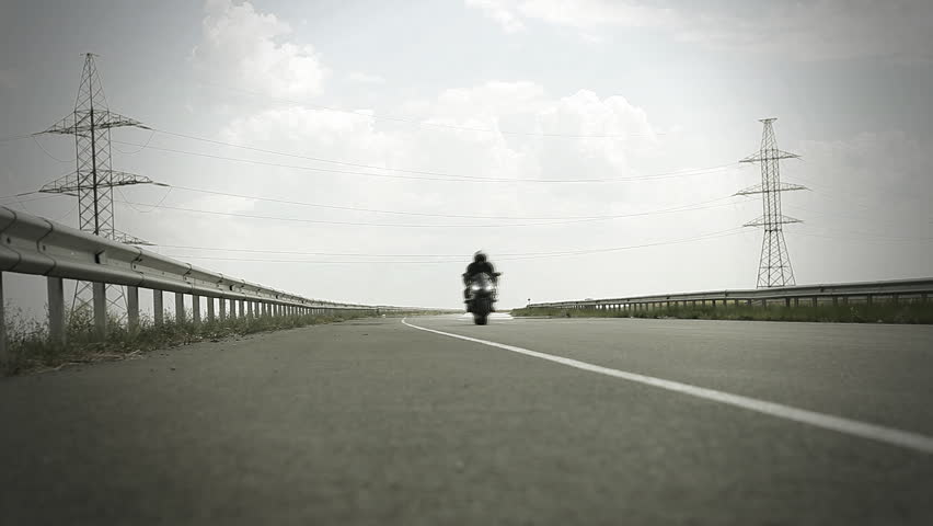 Man sitting on the motorcycle and moving on the road. | Shutterstock HD Video #4970774