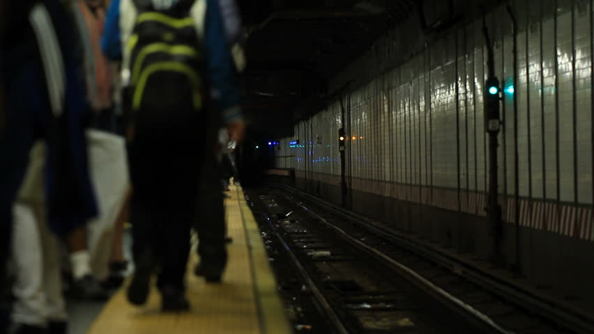 NYC subway train arriving to platform and people exiting & entering train to blackout screen. Camera 8 inches away from train while it goes by.