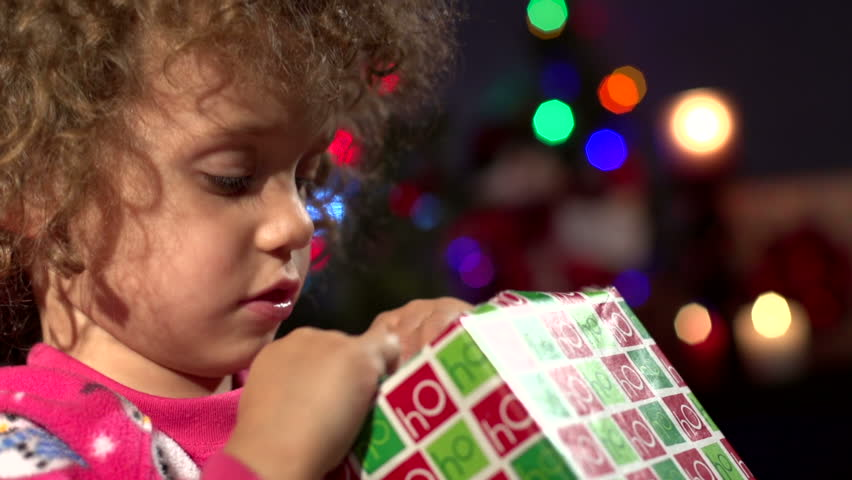 Close up of little girl opening Christmas present
