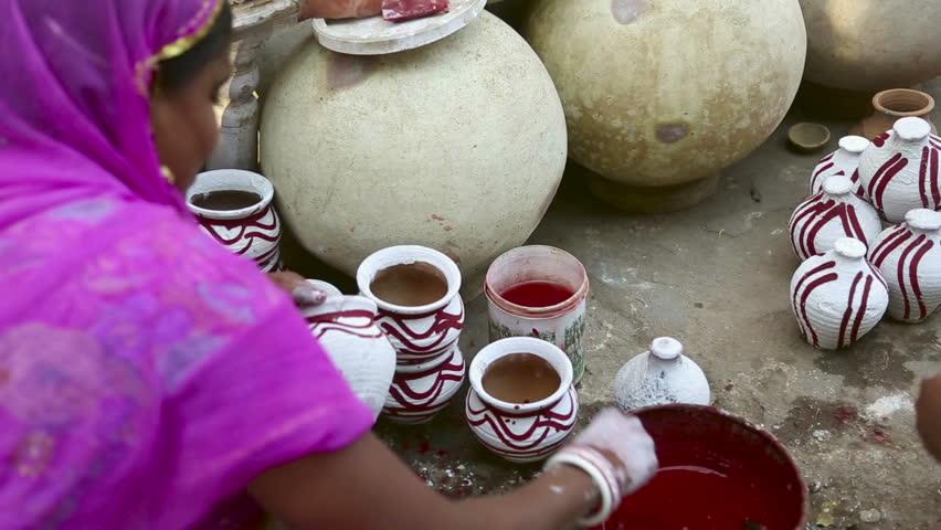 JODHPUR, INDIA - NOVEMBER 26, 2012 : City market of Jodhpur at 26, November 2012. Indian women painting ceramic pots in the street of Jodhpur, Rajasthan, India.