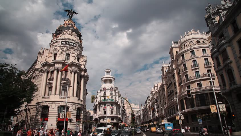 MADRID, SPAIN - AUGUST 12: People crossing Gran Via Street besides Metropolis Building, constructed in 1911 by Jules and Raymond Fevrier in new Renaissance style, on August 12, 2013 in Madrid, Spain