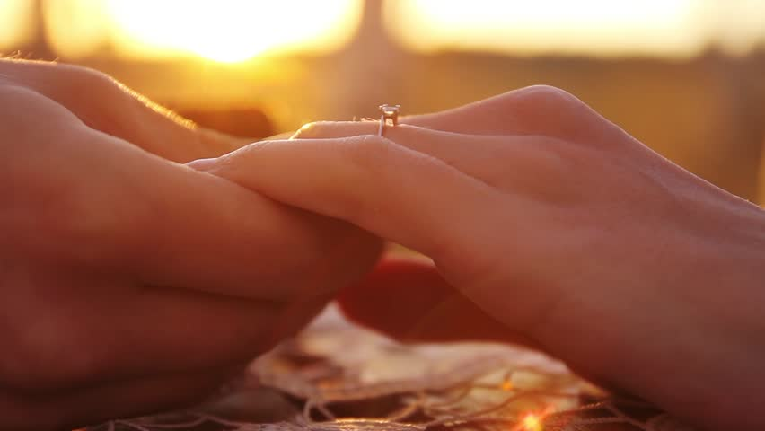 Proposal Putting on Engagement Ring at sunset close up hands