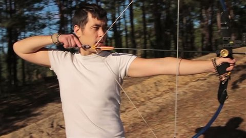 The young man is shooting from the sports bow in a sunny forest. 
