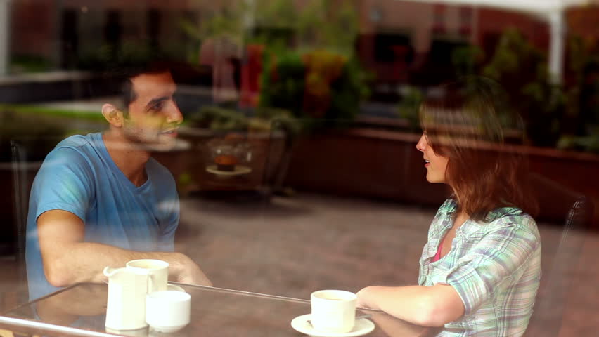 Couple chatting together in the canteen having coffee in college