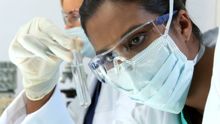 Close up of female scientist examines a test tube