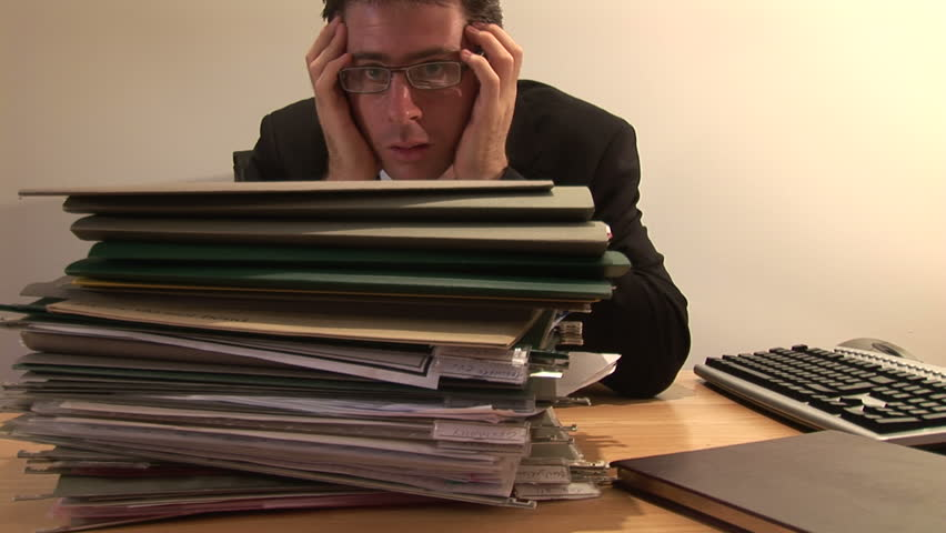 Businessman Staring at Pile of Paperwork