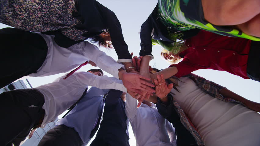 Motivational business team stand in a circle with their hands together for a team talk, outdoors in the city on a bright sunny day. In slow motion. | Shutterstock HD Video #5109362