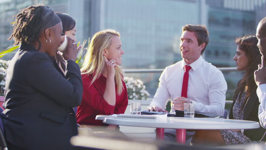 Happy and attractive mixed ethnicity business team sit and chat together on an open air city roof terrace. In slow motion. | Shutterstock HD Video #5109428