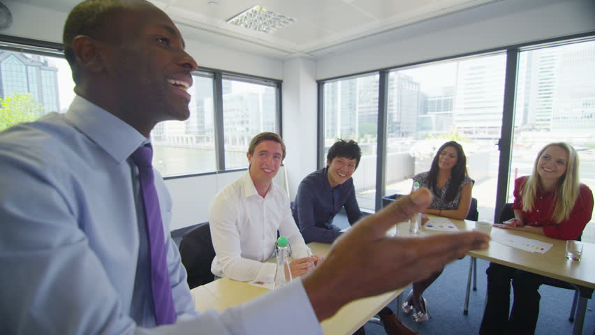 Attractive mixed ethnicity business team in boardroom meeting or training seminar. | Shutterstock HD Video #5110424
