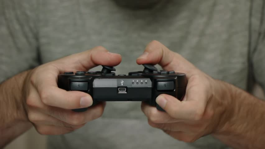 Man playing with a videogame controller in his hands. Focus on the controller