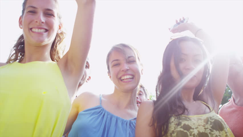 Fun loving group of young friends dancing together outdoors on a bright summer day. In slow motion.