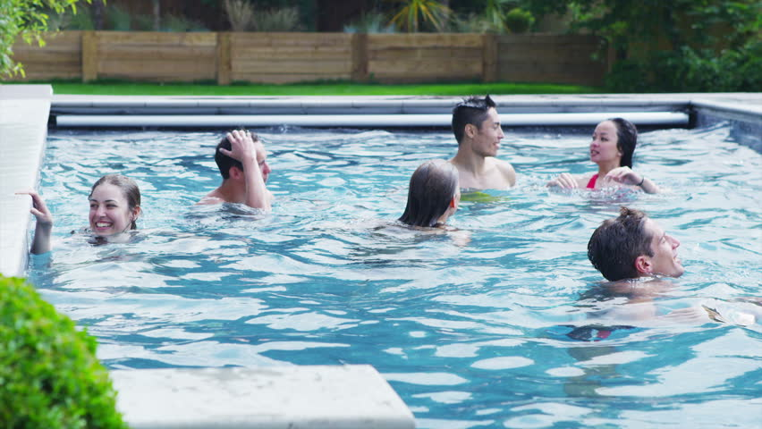Attractive young friends hanging out together in a pool outdoors on a summer day. In slow motion.