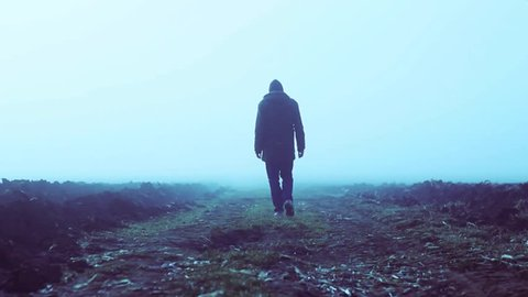 A lonely man walking into a foggy field in slow motion.